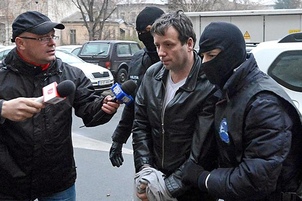 "Marcel Lazar Lehel, 40, is escorted by masked policemen in Bucharest, after being arrested in Arad, 550 km (337 miles) west of Bucharest January 22, 2014. Lehel is allegedly the hacker using the nicknames ""Guccifer"" and ""The Small Fume"" and is suspected to have broken into several e-mail accounts of various politicians and celebrities and the head of Romania's Intelligence Service George Maior. Credit: REUTERS/Mediafax/Silviu Matei"