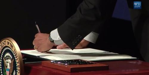 President Barack Obama signs an executive order at the Summit on Cybersecurity and Consumer Protection at Stanford University.